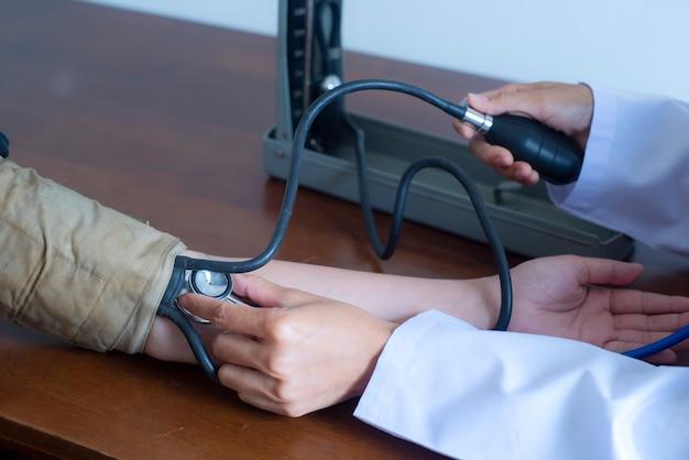 Schließen sie herauf die hand des doktors und des patienten unter verwendung des messens des arteriellen blutdrucks