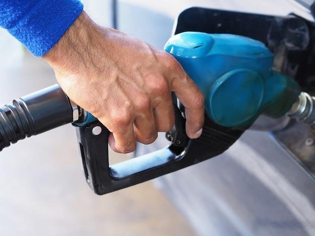 Schließen sie herauf die hand des mannes benzinkraftstoff im auto an der tankstelle pumpend.