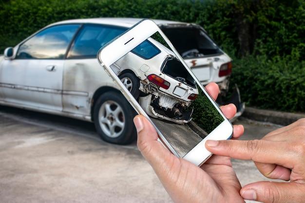 Schließen sie herauf die hand des mannes smartphone halten und machen sie foto des autounfalls