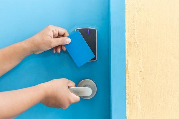 Schließen sie herauf die hand, die blaues hotel keycard vor elektrischer tür hält