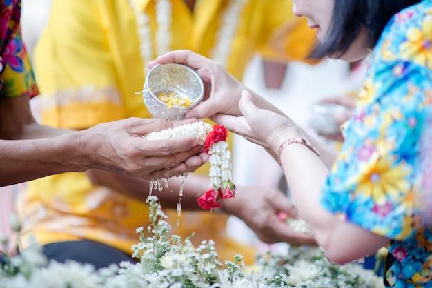 Schließen sie herauf die hand, die blume an der songkan-tradition von thailand hält