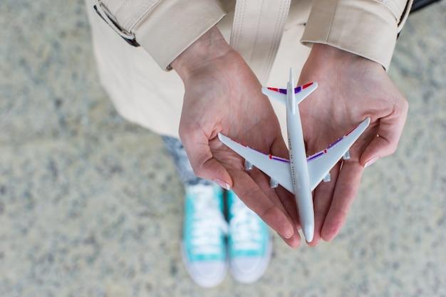 Schließen sie herauf die hand, die ein flugzeugmodell hält