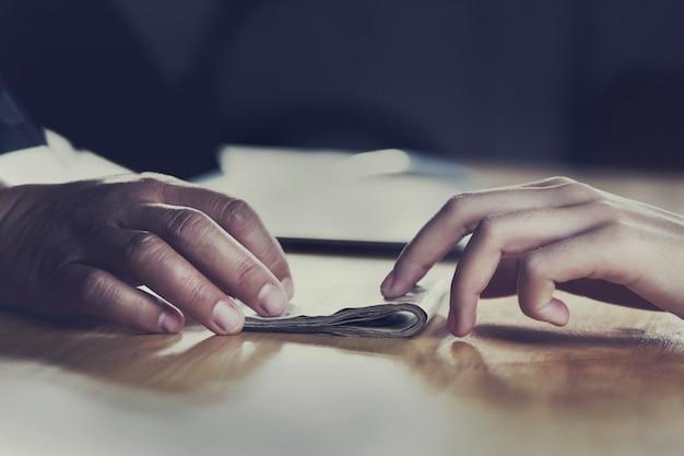 Schließen sie herauf die hand, die geld für partner auf schreibtisch gibt