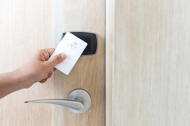 Schließen sie herauf die hand, die weiße hotelschlüsselkarte vor elektrischer tür hält