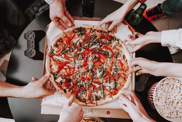 Schließen sie herauf die junge firma, die pizza auf partei isst