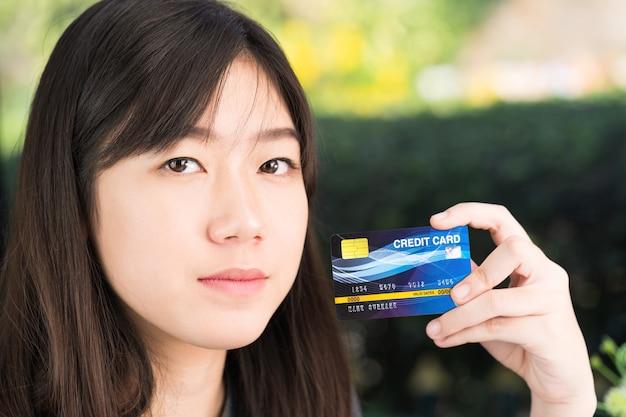 Schließen sie herauf die junge frau, die kreditkarte hält