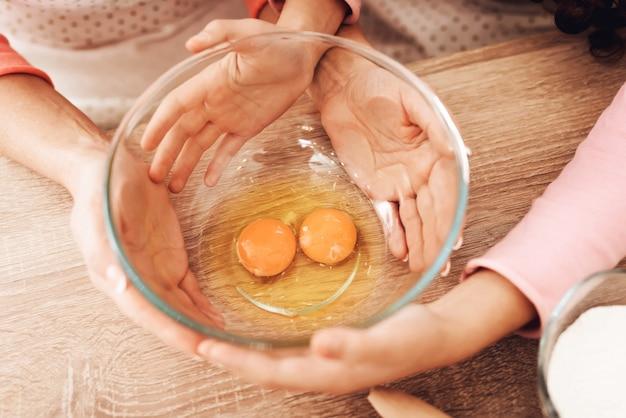 Schließen sie herauf die kinderhände, die schüssel mit eiern halten