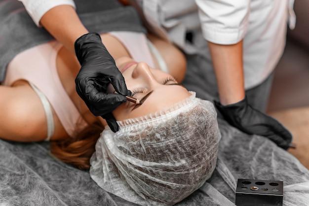 Schließen sie herauf die kosmetikerhände, die augenbrauentätowierung auf frauengesicht tun. permanentes brauen-make-up im schönheitssalon. spezialist, der die augenbraue tätowiert für weibliches gesicht tut. kosmetologische behandlung.