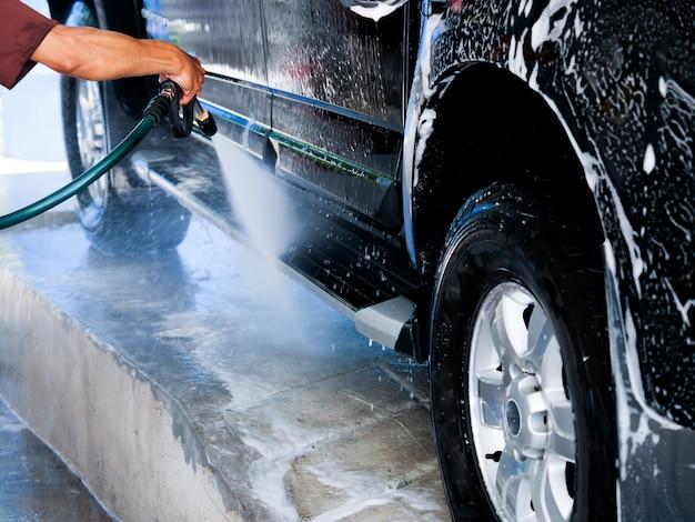 Schließen sie herauf die leichtmetallräder der mannhändearbeitskraft, die auto an der garage waschen