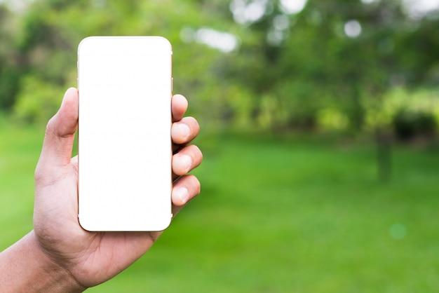 Schließen sie herauf die männliche hand, die leeren bildschirm des smartphone auf parkhintergrund hält.