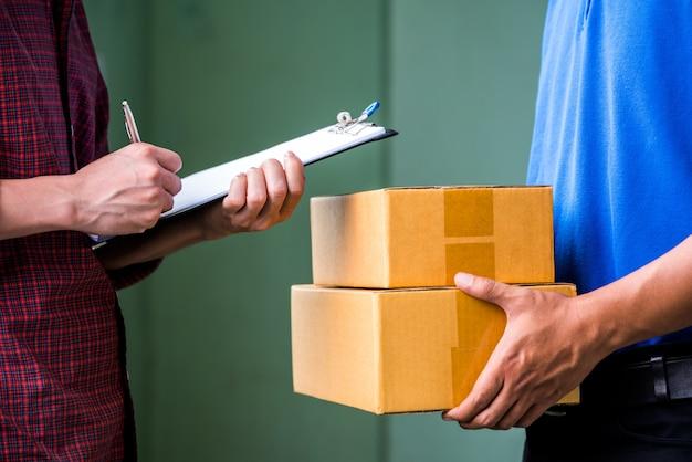 Schließen sie herauf die mannhände, die unterzeichnen, um sein paket vom lieferboten zu erhalten.