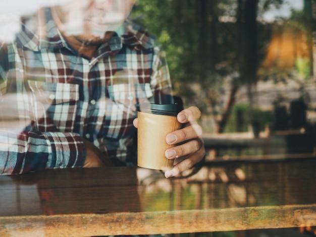 Schließen sie herauf die mannhand, die kaffeetasse hält.