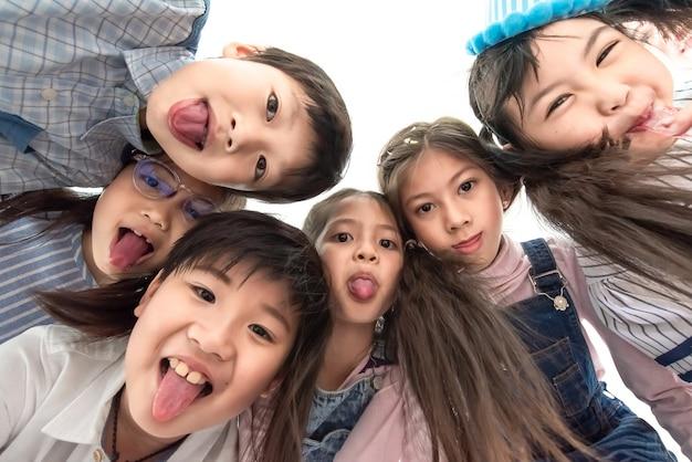 Schließen sie herauf die multiethnische gruppe kinderschulkinder, die zur kamera umfassen und lächeln
