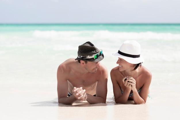 Schließen sie herauf die paare, die einander auf dem strand betrachten