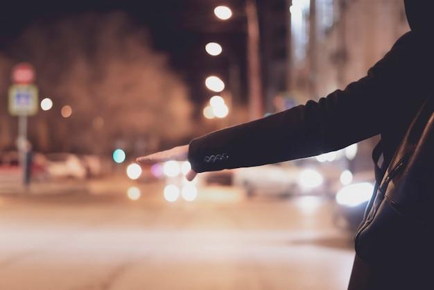 Schließen sie herauf die personenhand, die per anhalter fährt und auf einen autostand auf einer landstraße in der nacht wartet