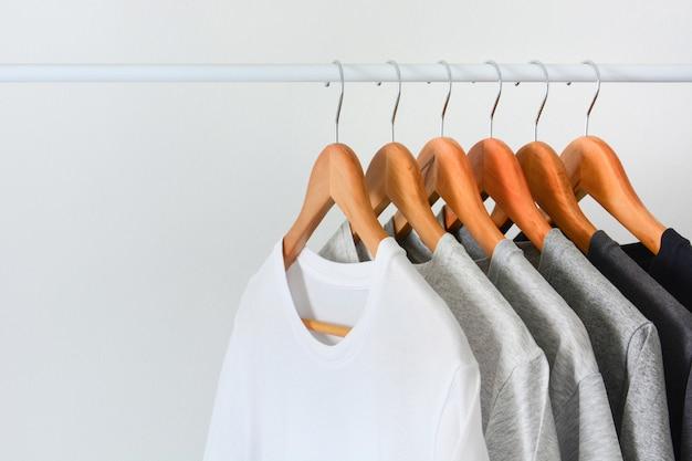 Schließen sie herauf die sammlung der schwarzen, grauen und weißen farbe (monochrom), die am hölzernen kleiderbügel hängt