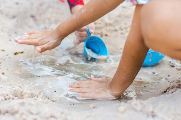 Schließen sie herauf die schmutzigen hände eines kleinen jungenkindes, das in den spielenden sand gräbt, ist ein glückliches