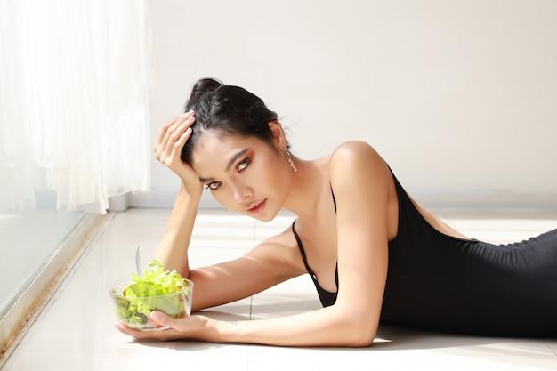 Schließen sie herauf die schöne gesunde und sportliche asiatische junge frau, die salatschüssel hält und essen sie nach der ausbildung