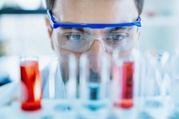 Schließen sie herauf die schützenden augengläser der wissenschaftlerabnutzung, die medizinischen test im glasrohr beim handeln der forschung im wissenschaftlichen labor betrachten
