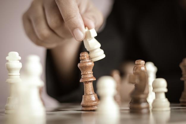 Schließen sie herauf die schusshand der geschäftsfrau das schachbrett spielend wählen flache schärfentiefe des fokus aus