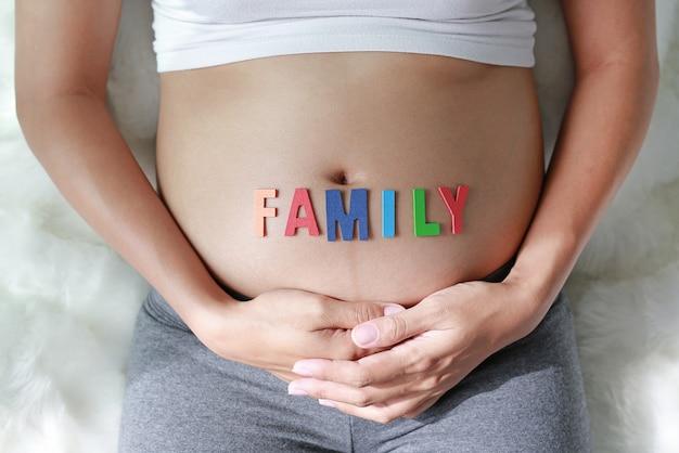 Schließen sie herauf die schwangere frau, die auf weichem sofa sitzt und ihren bauch mit zeichen familie vor ihrem bauch berührt.