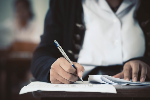 Schließen sie herauf die studenten, die prüfungsantwortblattübungen im klassenzimmer der schule mit druck schreiben und lesen.