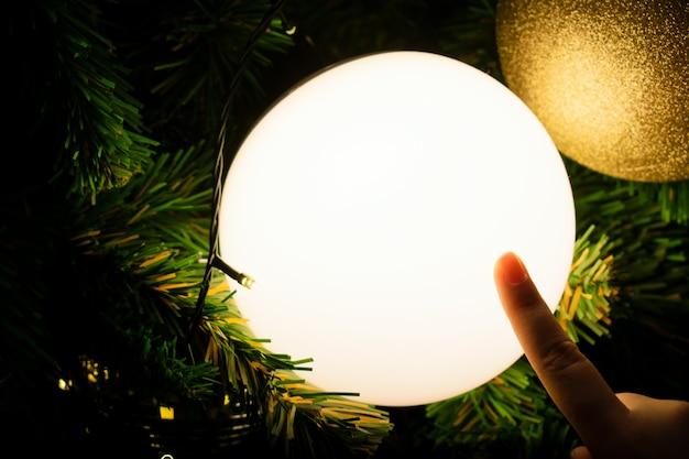 Schließen sie herauf die weibliche hand, die eine helle kugel berührt. geschmückter weihnachtsbaum in silber