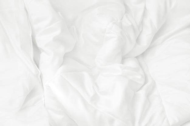 Schließen sie herauf draufsicht des weißen bettwäscheblattes und unordentliche decke der falte im schlafzimmer.