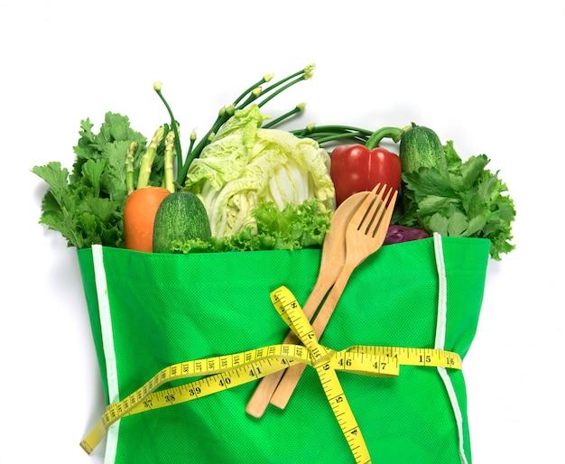 Schließen sie herauf eine grüne einkaufstüte des gemischten organischen grünen gemüses auf weißem, gesundem einkauf des organischen grünen lebensmittels und diätgesundheitswesen-ernährungstherapie