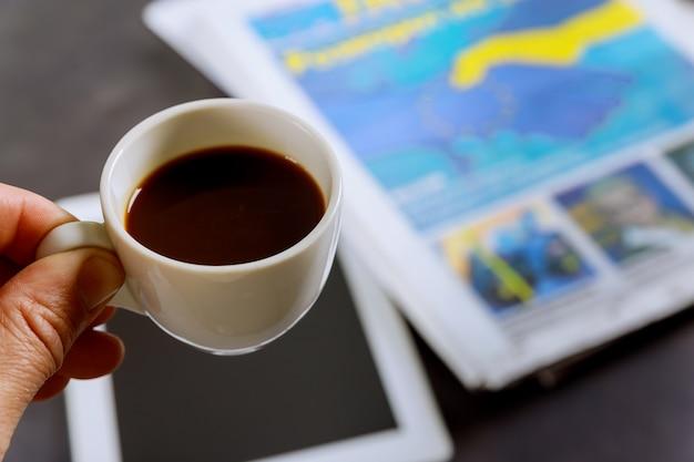 Schließen sie herauf espressokaffeetasse auf zeitung die tabelle