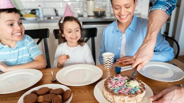 Schließen sie herauf familie, die mit kuchen feiert