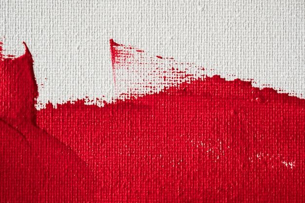 Schließen sie herauf farbe der beschaffenheit rote farbauf weißem segeltuchhintergrund