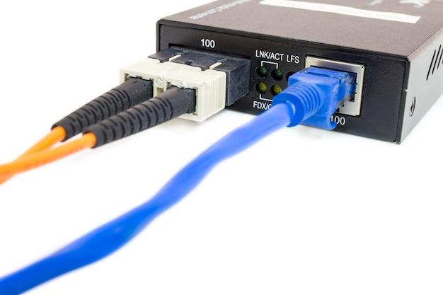 Schließen sie herauf fasermedienkonverter und -kabel auf weißem getrenntem hintergrund