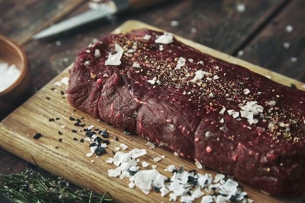 Schließen sie herauf fokussiertes stück fleisch gesalzen, das auf holzbrett auf vintage-tisch zwischen gewürzen gepfeffert wird