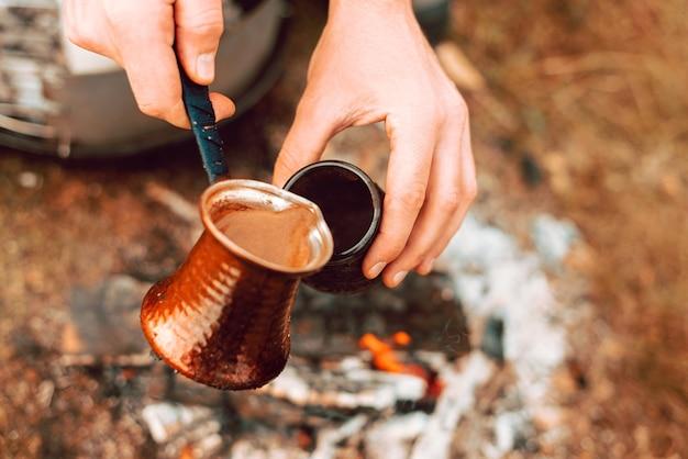 Schließen sie herauf foto auf einer türkischen kaffeekanne, die in eine tasse auf einem feld am morgen gießt