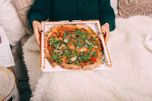 Schließen sie herauf foto der frau, die im bett sitzt und große rucola-pizza hält. lieferung pizza konzept
