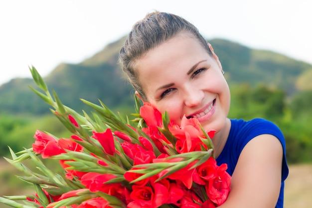 Schließen sie herauf foto der glücklichen schönen hübschen schönen jungen jungen fröhlichen frau, die mit nettem rotem strauß von gladiolen, gladiolen draußen lächelt. internationaler frauentag, naturkonzept