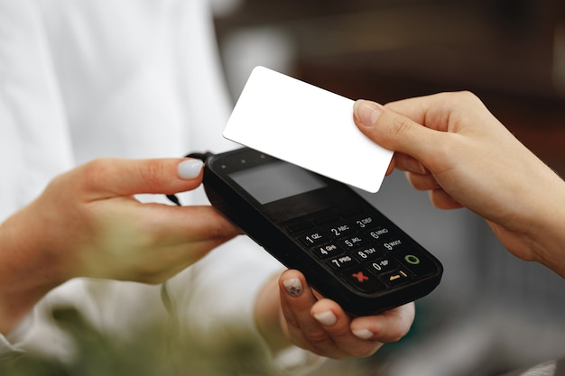 Schließen sie herauf foto der hand des kunden, der mit kontaktloser kreditkarte zahlt