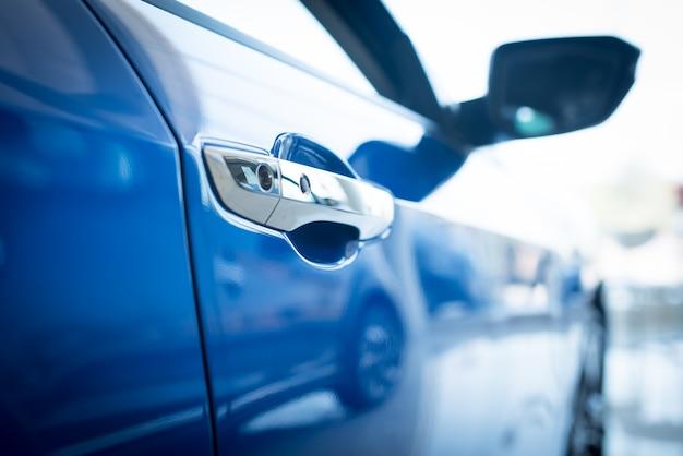 Schließen sie herauf foto der neuen blauen autotür. konzept für die autovermietung., neue autos zum verkauf angeboten, im ausstellungsraum geparkt.