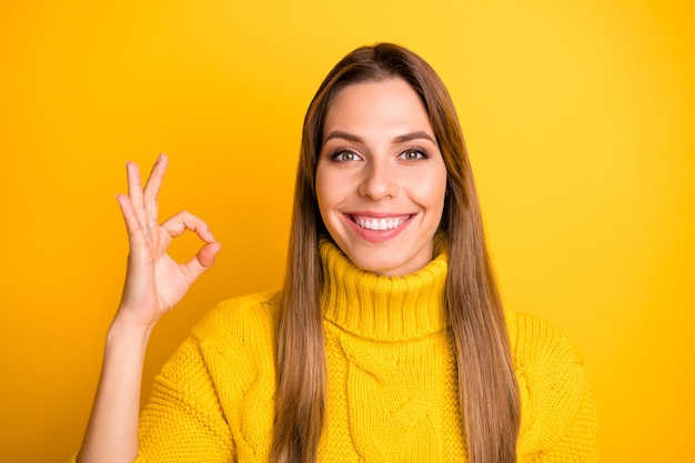 Schließen sie herauf foto der positiven fröhlichen mädchen promoter show okay zeichen empfehlen pick werbung promotion tragen lässigen stil pullover über glanz farbe wand isoliert