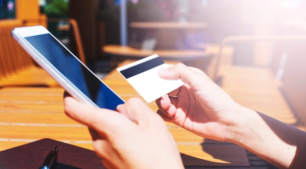 Schließen sie herauf foto der weiblichen hände unter verwendung des smartphones und der kreditkarte für online-einkauf