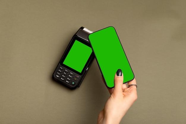 Schließen sie herauf foto der weiblichen hand, die mit smartphone nfc zahlt