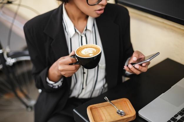 Schließen sie herauf foto des afroamerikanischen mädchens, das am tisch des cafés mit handy und tasse kaffee in den händen sitzt