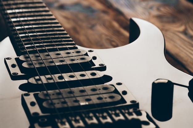 Schließen sie herauf foto des e-gitarrengriffbretts auf dunklem hintergrund