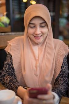Schließen sie herauf foto des einzelnen moslemischen frauenkleides mit dem braunen hijab, der handy spielt