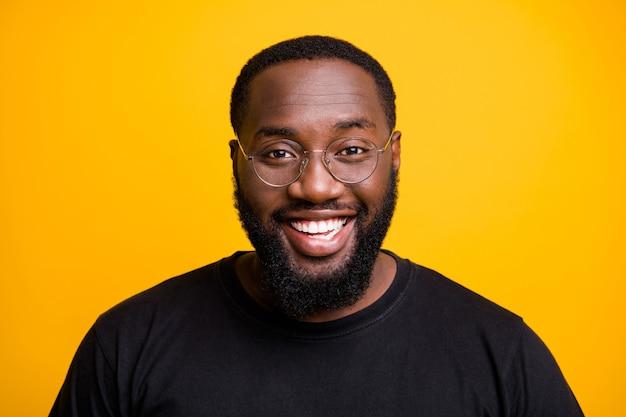 Schließen sie herauf foto des fröhlichen positiven attraktiven schwarzen mannes mit weiß gewordenen zähnen, die sie mit lächeln auf gesicht lokalisierte lebendige farbwand betrachten