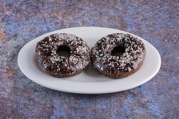 Schließen sie herauf foto des hausgemachten donuts auf weißem teller