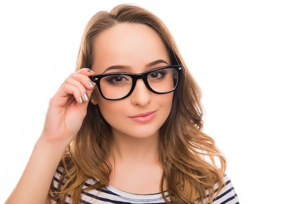 Schließen sie herauf foto des hübschen klugen mädchens, das ihre brille berührt