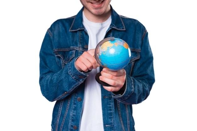 Schließen sie herauf foto des jungen mannes, der auf globus zeigt