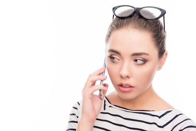 Schließen sie herauf foto des niedlichen mädchens, das am telefon mit brille auf kopf spricht